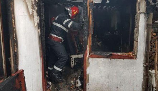 Foto: Femeie şi copil de trei ani, găsiți cu gâtul tăiat într-o locuință incendiată