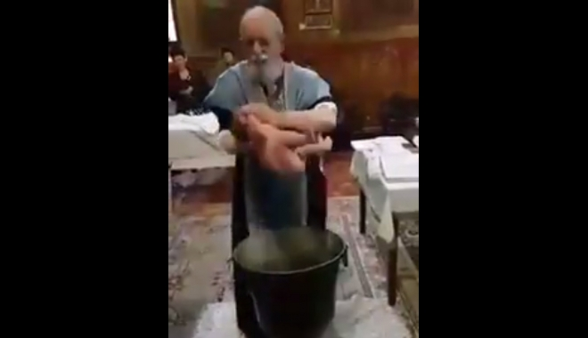 VIDEO ŞOCANT / Botez de COŞMAR. Bebeluş confundat de preot cu un sac de cartofi