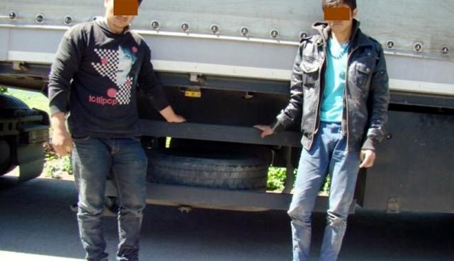 Foto: Doi afgani, descoperiţi sub un tir, la Ostrov