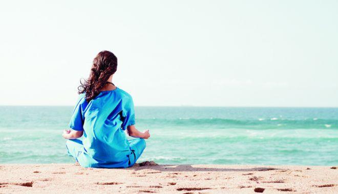 Foto: Exerciţii de yoga, dimineaţa, pe malul mării