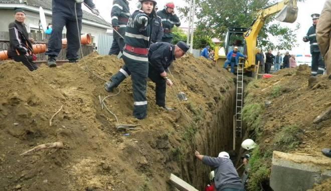 Foto: Trei muncitori care lucrau la execuția unei canalizări, prinși sub un mal de pământ