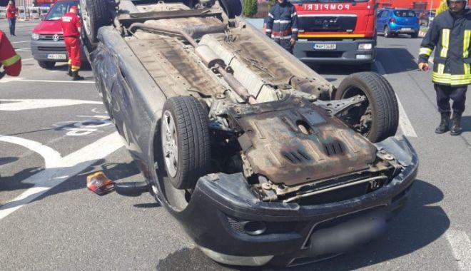 Foto: Accident în parcarea unui supermarket. O mașină, răsturnată