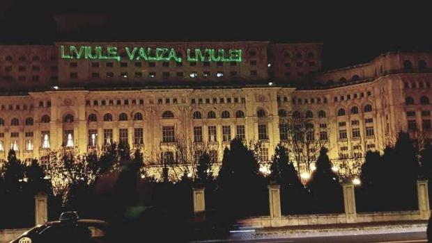 """Foto: """"Liviule, valiza, Liviule"""", proiecţie laser pe clădirea Palatului Parlamentului. Protestul, oprit de jandarmi"""