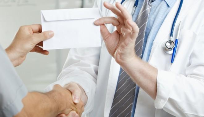 Foto: Medic prins în timp ce primea mită de la două studente
