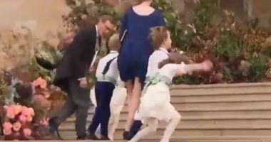 Prințesa Charlotte și un băiat de onoare, luați de vânt pe scările de intrare în biserică, la nunta prințesei Eugenie
