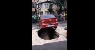 Maşină căzută într-o groapă după ce asfaltul de sub ea s-a surpat
