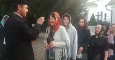 VIDEO. Credincioşi plesniţi peste ochi cu aghiasmă, în curtea unei mănăstiri